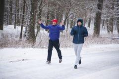 哥罗德诺,白俄罗斯- 2017年1月15日 两个年轻人参与奔跑在冬天森林里 免版税图库摄影