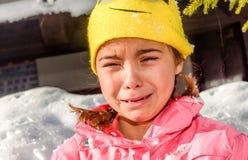 哭泣一个的小女孩的画象,因为她是冷的在雪 免版税库存照片