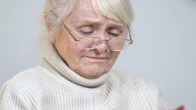 哭泣不快乐的年长的夫人看在册页的照片,记住那时候 影视素材