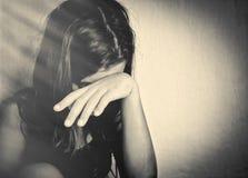 哭泣与现有量覆盖物的孤独的女孩她的表面 库存图片