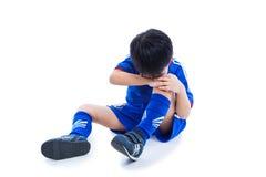 哭泣为痛苦的膝伤的青年亚裔足球运动员 充分 库存图片