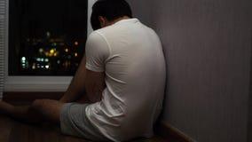 哭泣和坐由一个窗口在晚上 影视素材