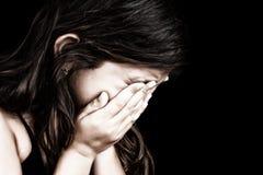 哭泣和隐藏她的表面的女孩的纵向 免版税库存图片