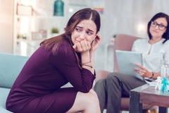 哭泣在参观期间的哀伤的悲哀迷人的妇女对心理学家 免版税库存图片