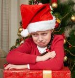 哭泣在圣诞树附近的不快乐的女孩,穿戴在红色和圣诞老人帽子 免版税库存照片