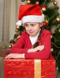 哭泣在圣诞树附近的不快乐的女孩,穿戴在红色和圣诞老人帽子 免版税库存图片