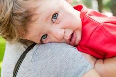 哭泣在她的母亲的手的小孩子 免版税库存图片