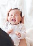 哭泣在她的母亲的胳膊的新出生的婴孩 免版税库存图片