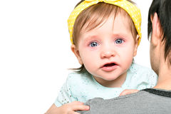 哭泣在她的父亲的手上的一个逗人喜爱的小女孩的画象 免版税库存图片