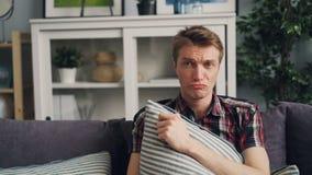 哭泣在对负的电视的哀伤的电影的情感年轻人放大坐舒适的沙发和遥控和 股票视频