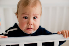 哭泣在小儿床的婴孩 图库摄影