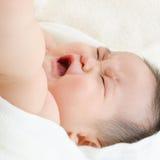 哭泣在床上的亚裔男婴 免版税库存图片