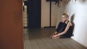 哭泣在损失perfomance以后的年轻十几岁的女孩舞蹈家特写镜头坐地板在大厅里户内 库存图片