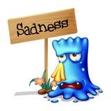 哭泣在木标志附近的一个非常哀伤的蓝色妖怪 库存照片