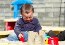 哭泣在沙盒的一个小男孩 被弄脏的焦点 库存图片