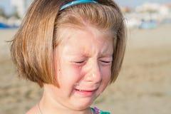 哭泣在海滩的小女孩 免版税库存图片