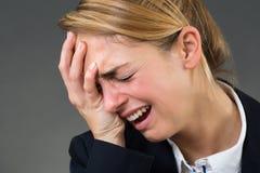 哭泣在灰色背景的女实业家 免版税库存照片