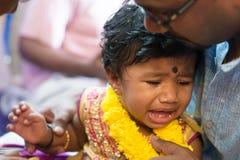 哭泣在耳朵贯穿的仪式的女婴 免版税库存图片
