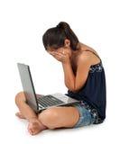 哭泣在膝上型计算机前面的十几岁的女孩 免版税库存图片