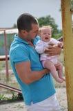 哭泣在年轻父亲的手上的小小儿童孩子室外在夏天 免版税库存照片