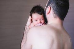 哭泣在他的父亲肩膀的男婴 库存照片