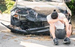 哭泣在他的老损坏的汽车的绝望人在崩溃以后 免版税库存照片