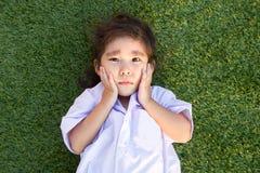 哭泣在绿草的亚裔泰国孩子 免版税库存图片