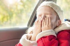 哭泣小的女孩,当旅行在汽车座位时 免版税库存照片