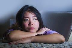 哭泣年轻哀伤和沮丧的亚洲韩国妇女在家沙发的长沙发绝望和无能为力的遭受的忧虑和消沉feeli 免版税图库摄影