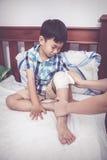 哭泣的孩子受伤 包扎儿子` s膝盖的母亲 葡萄酒口气 库存照片