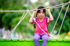 哭泣的小亚裔女孩单独坐操场 免版税库存照片