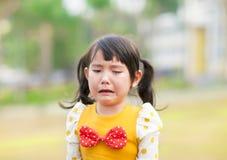 哭泣的小女孩在公园 免版税库存照片