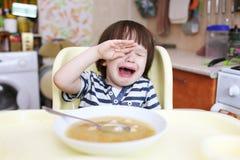 哭泣的小男孩不要在家吃浓豌豆汤 免版税库存图片