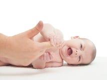 哭泣的小白种人男婴握妇女手指 图库摄影