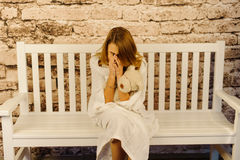 哭泣的少年在被编织的格子花呢披肩被包裹,当坐长凳时 图库摄影