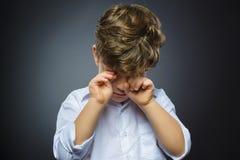 哭泣的男孩特写镜头画象有吃惊的表示的,当站立反对灰色背景时 免版税图库摄影