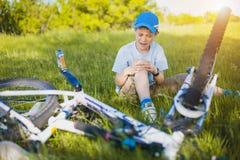 哭泣的男孩以在自行车附近的出血伤害 免版税库存照片