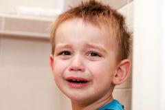 哭泣的男婴画象在家 免版税库存图片