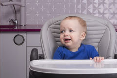 哭泣的婴儿孩子在有现代设计的厨房里 库存图片