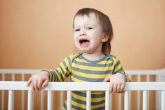 哭泣的婴孩在床上 库存照片
