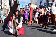 哭泣耶稣基督的作用在运载在街道上的痛苦和极度痛苦重的木十字架 免版税库存照片