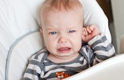 哭泣逗人喜爱的小男孩握他的耳朵 免版税库存照片