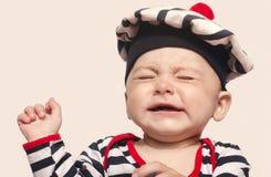 哭泣逗人喜爱的男婴举他的手  免版税库存图片