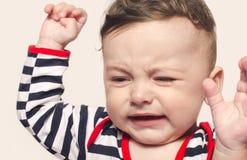 哭泣逗人喜爱的男婴举他的手  免版税库存照片
