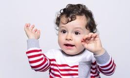 哭泣逗人喜爱的男婴举他的手  图库摄影