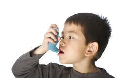 哮喘男孩逗人喜爱他的吸入器使用年&# 免版税图库摄影