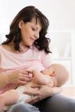 哺乳和拥抱她的婴孩的母亲户内 图库摄影