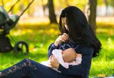 哺乳在美好的春天光的母亲 免版税库存图片