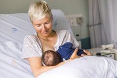 哺乳她新出生的男婴的妈妈在医院 库存图片