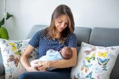 哺乳她新出生的男婴的年轻母亲 库存照片